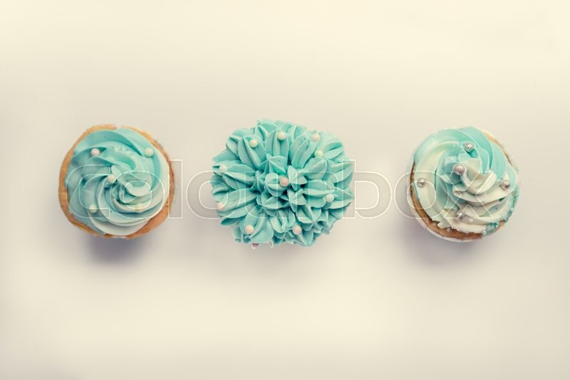 Stock image of 'Pearl birthday cupcake with butter cream icing on gray background, top view.'