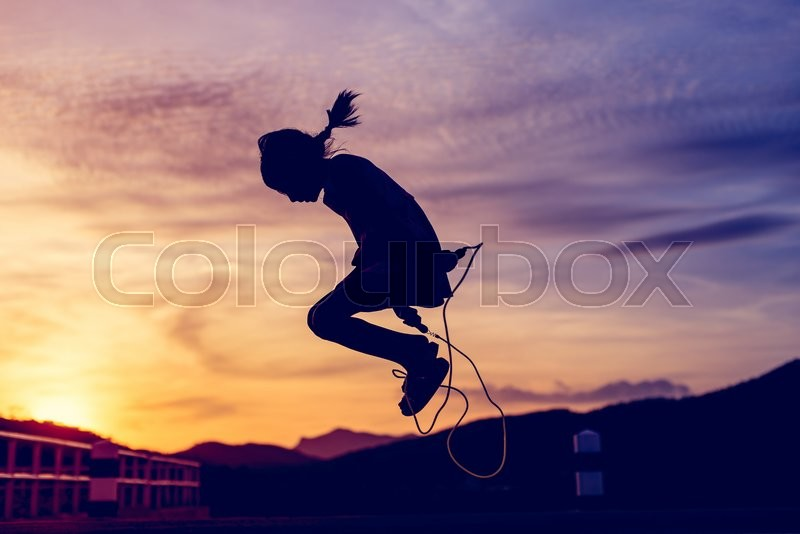 Stock image of 'Girl  jumping rope in silhouette with sun set'