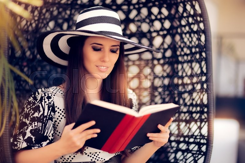 Stock image of 'Portrait of a beautiful girl with a book and big sunhat'