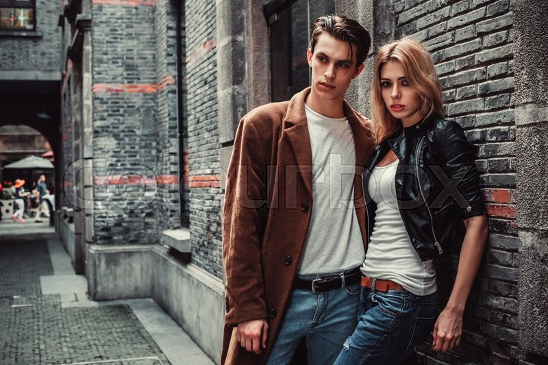 Stock image of 'Young and trendy man and woman posing of the street with brick walls. Fashion style'