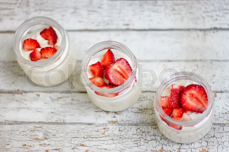 Stock image of 'Dairy products with strawberry on white wooden table'