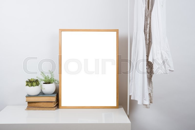 Stock image of 'Empty wooden picture frame on the table in white room interior, art print design ready mock-up'