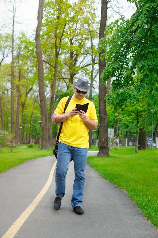 Stock image of 'happy man with a hat, yellow T-shirt and phone is walking in the park.'