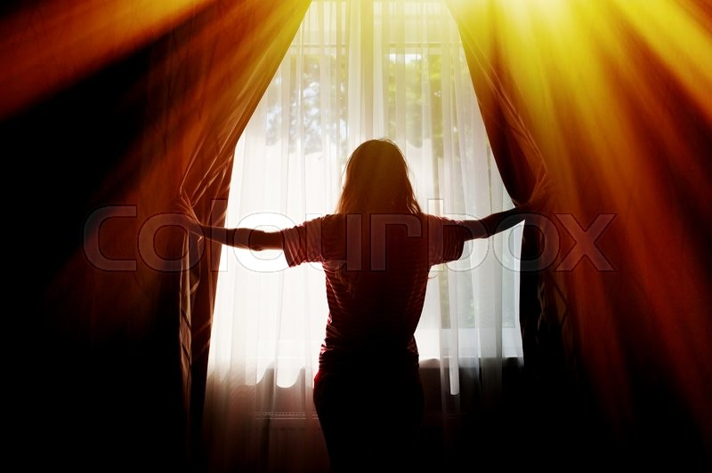 Stock image of 'Silhouette of a young woman opens curtains at window.'