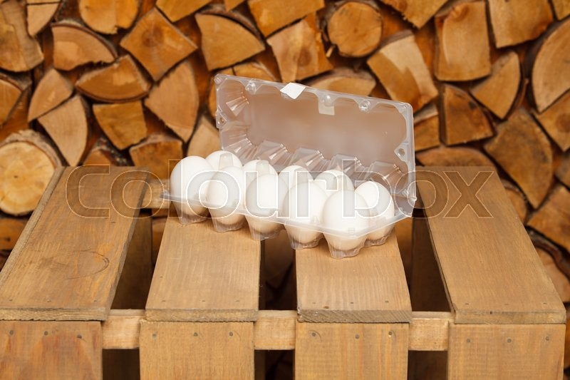 Stock image of 'Dozen of white eggs on brown wooden stand'