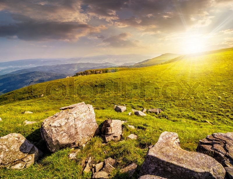 Stock image of 'white sharp boulders on the hillside meadow with green grass in high Crapathian mountains in evening light'
