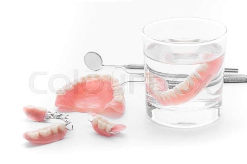 Stock image of 'Set of Denture in glass of water and tools  on white background'