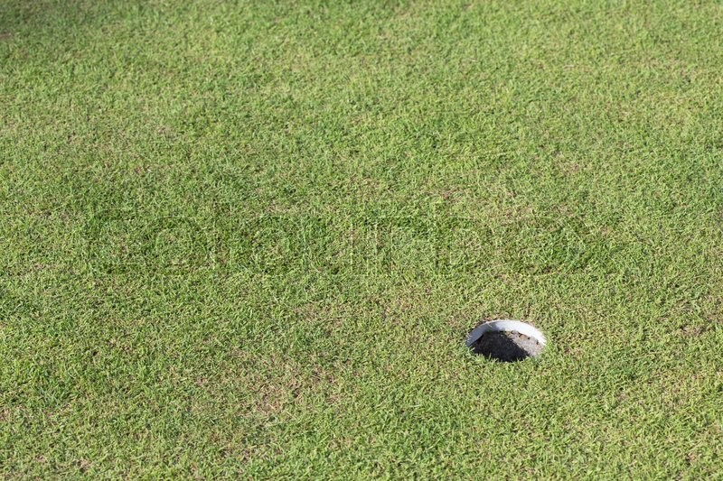 Golf hole on green grass, golf course, stock photo
