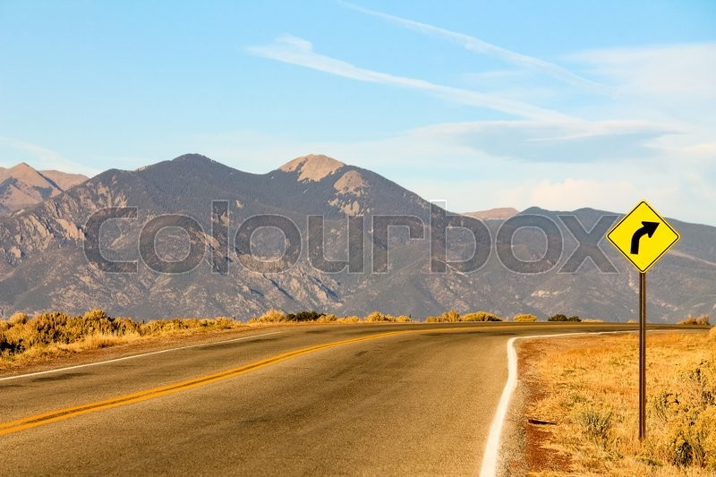 Stock image of 'A sign warns of a right curve ahead on a mountain road in Colorado near Aspen'