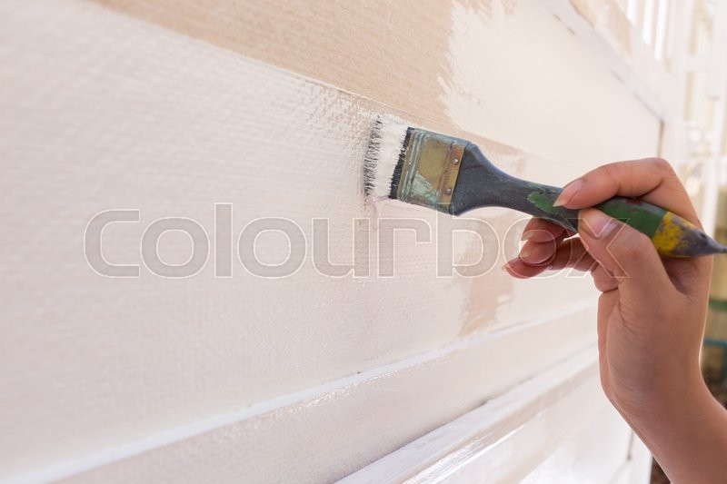 Stock image of 'Hand worker holding brush painting white on wood fence'