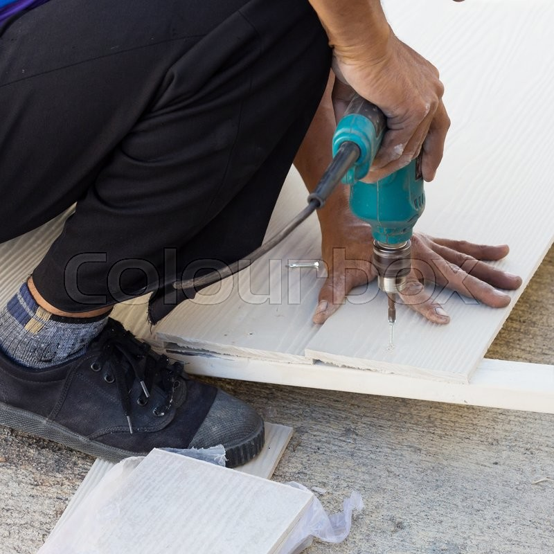 Stock image of 'Carpenter hands using electric drill on wood at construction site'