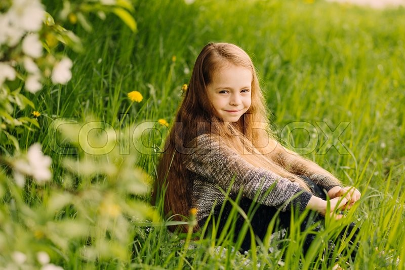 Stock image of 'Little cute fashionable long-haired brown-eyed girl sitting on the lawn in blossoming spring garden outdoor'