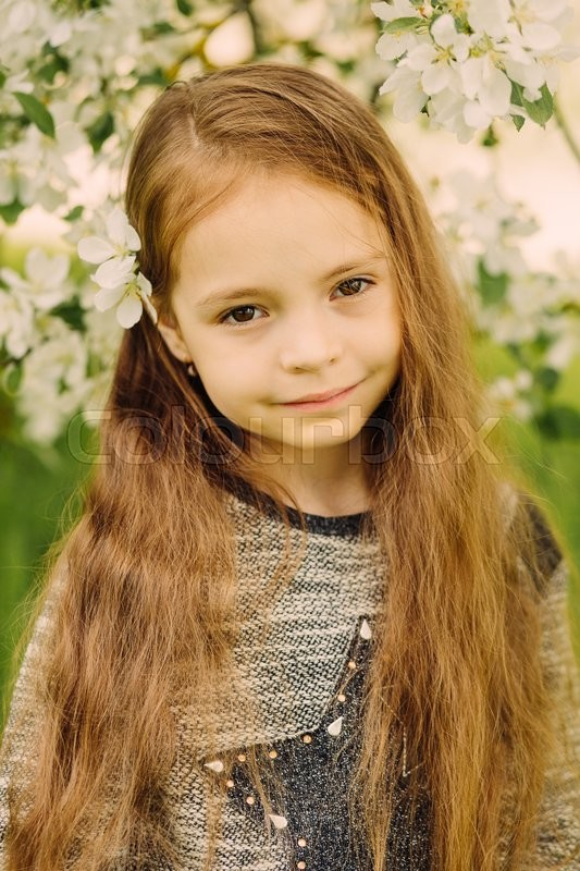Stock image of 'Little cute fashionable long-haired brown-eyed girl stanging in blossoming spring garden outdoor'