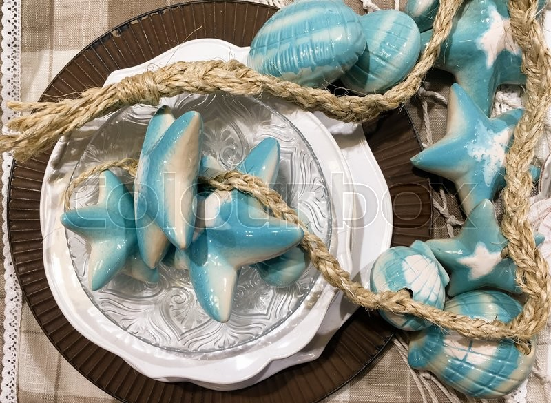 Stock image of 'Summer table decorations , a plate with starfish , seashells and a rope'