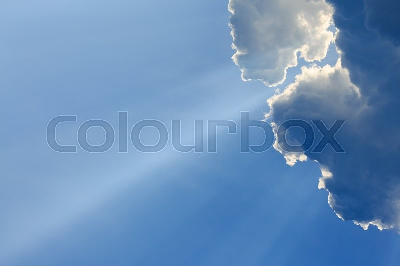 Stock image of 'light rays on clear blue sky'