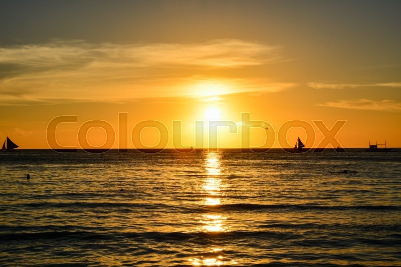Stock image of 'Sunset in Boracay, Philippines with people and some boats at the horizon'