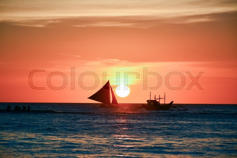 Stock image of 'Sunset in Boracay, Philippines with a boat in the foreground'