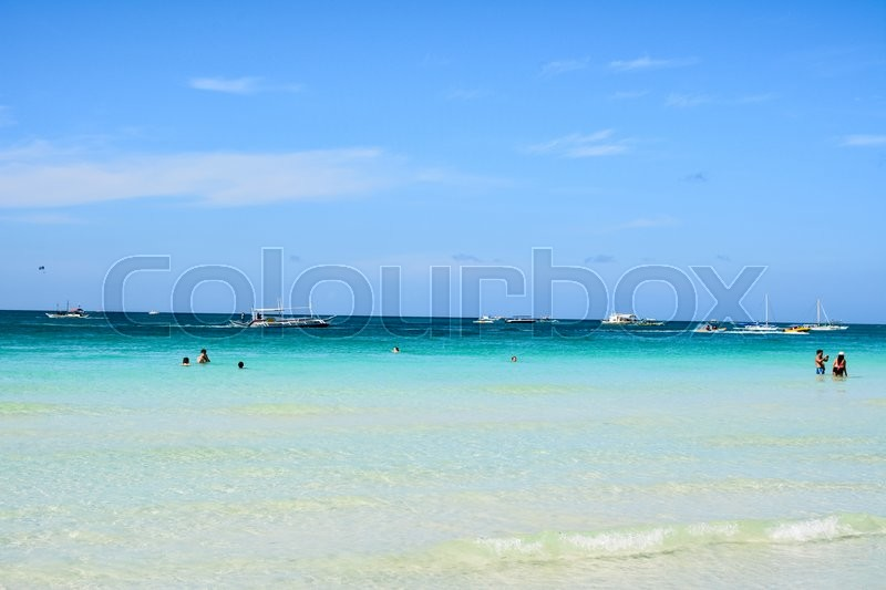 Stock image of 'BORACAY, PHILIPPINES - JANUARY 7 , 2015 - Some tourists swim and take pictures in the White Beach of Boracay with the boats behind them ready for the excursions.'