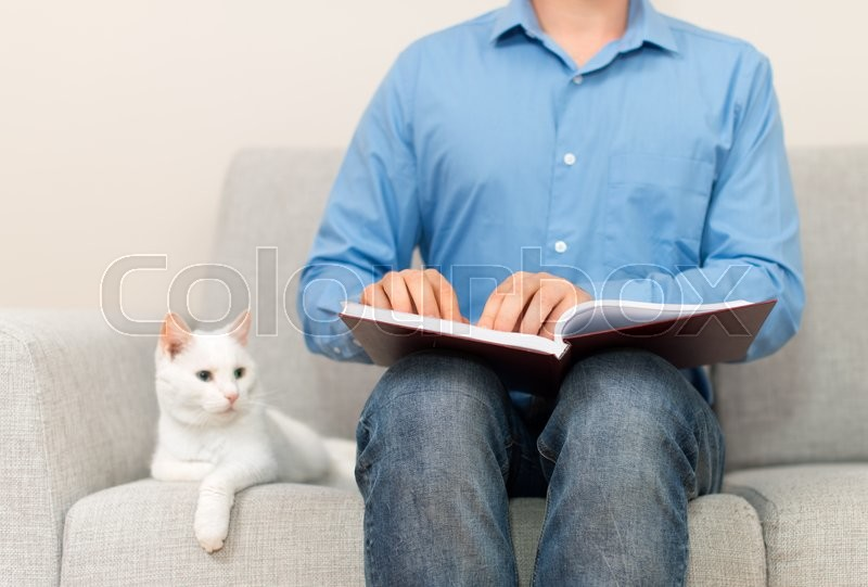 Stock image of 'Blind man reading braille book on the couch.'
