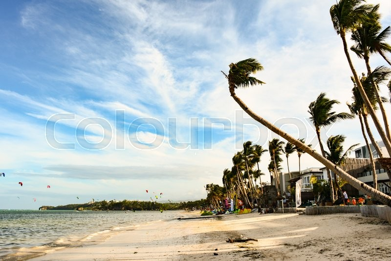 Stock image of 'BORACAY, PHILIPPINES - JANUARY 7, 2015 -  View of a beach in Boracay with some tourists who enjoy kite surfing.'
