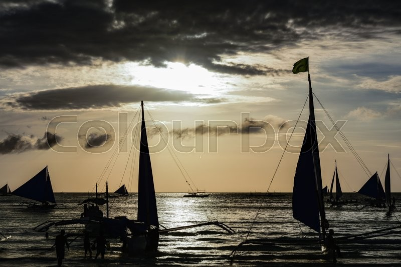 Stock image of 'Silhouette of some boats in foreground and people waiting for sunset in Boracay island, Philippines'
