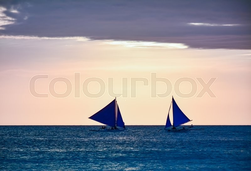 Stock image of 'BORACAY, PHILIPPINES - JANUARY 7, 2015 - Boats with some tourists watching the sunset from the sea in Boracay island, Philippines'
