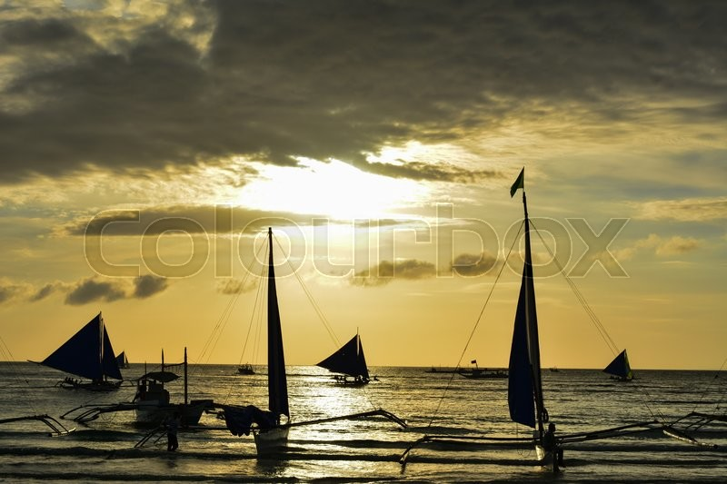 Stock image of 'Sunset in Boracay, Philippines with some boats in foreground'