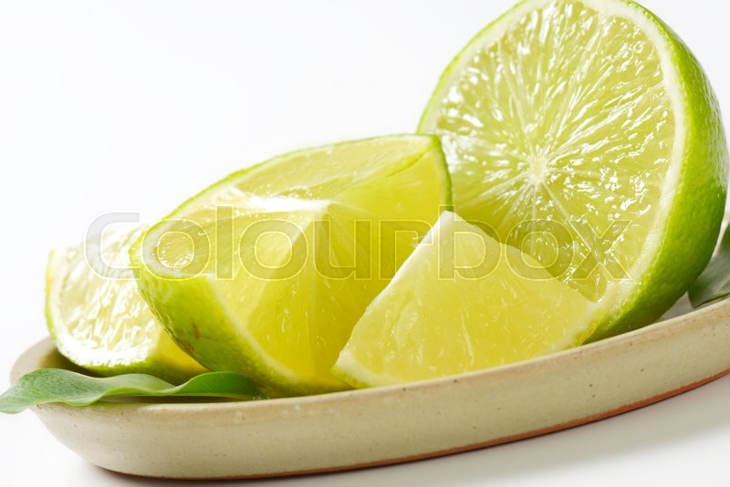 Stock image of 'Pieces of fresh lime  on oval plate'