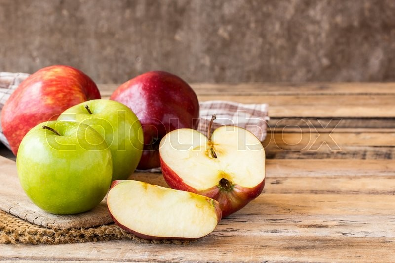 Stock image of 'Close up of a sliced red apple on a wooden table. Fresh red apple on old wooden table background. red and green apple on wood table'