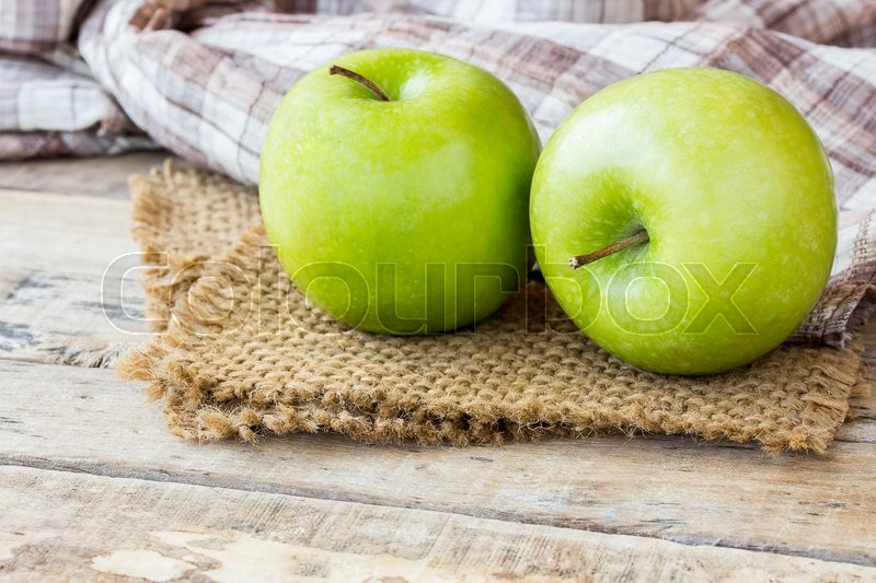 Stock image of 'Green apple with leaves on burlap, on old wooden table background. green apple for healthy eating and healhcare concept for design'