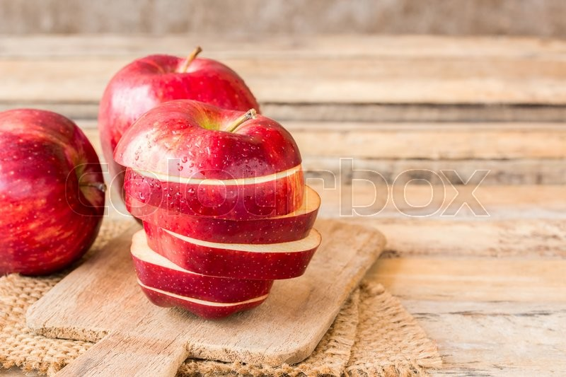 Stock image of 'Close up of a sliced red apple on a wooden table. Fresh red apple on old wooden table background. Red apple on wood table'