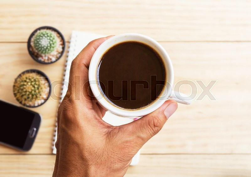 Stock image of 'Hand reaching for coffee mug and blurred smart phone,note book on wooden table background. Top view.'