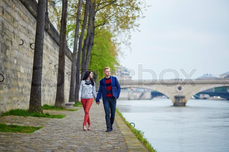 Stock image of 'Happy couple walking on the bank of the Seine in Paris. Tourists enjoying their vacation in France. Romantic date or traveling couple concept'