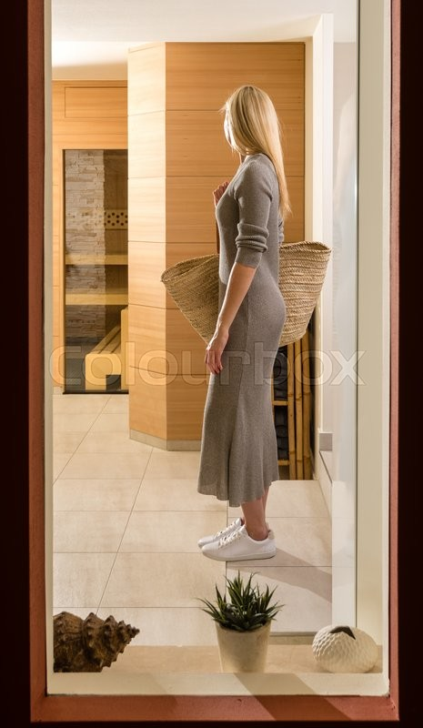 Stock image of 'Gorgeous blonde woman with a large bag is entering a spa center as seen through a window in the lobby'