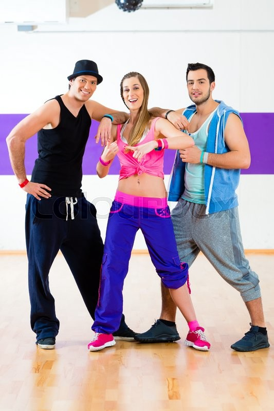 Stock image of 'Group of men and women dancing zumba fitness choreography in dance school'