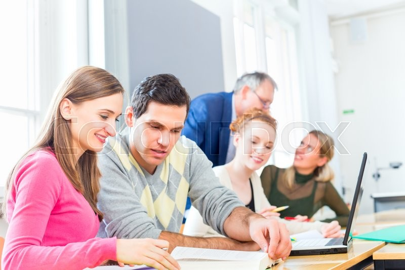 University college students with professor in seminar using laptop for project team work, stock photo