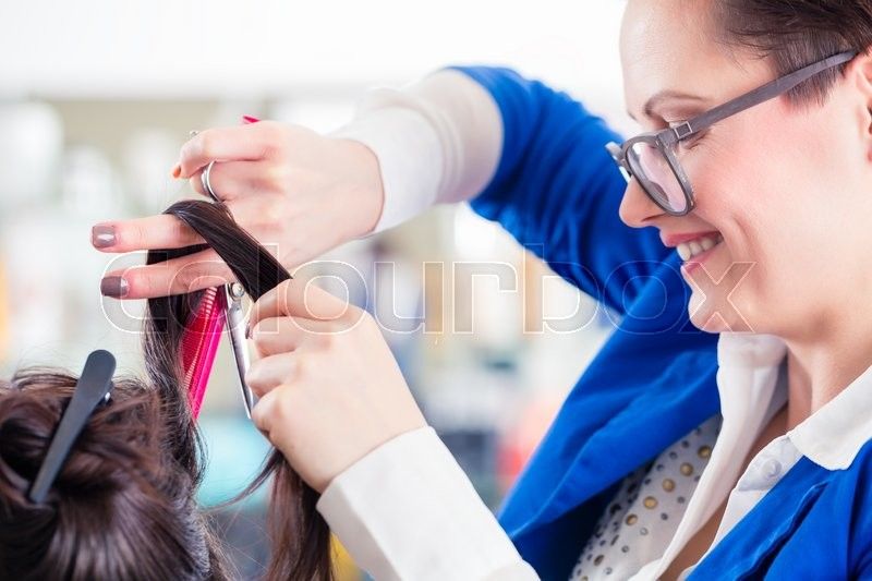 Stock image of 'Female coiffeur divide women hair in sections with clips in shop'