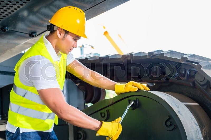 Stock image of 'Asian motor mechanic working on construction or mining machinery in vehicle workshop'