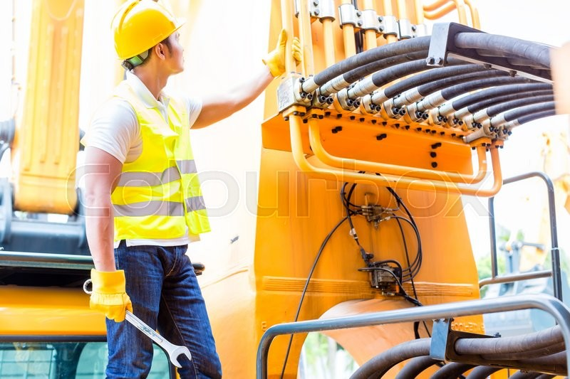 Stock image of 'Asian motor mechanic standing in front of construction or mining machinery in vehicle workshop'