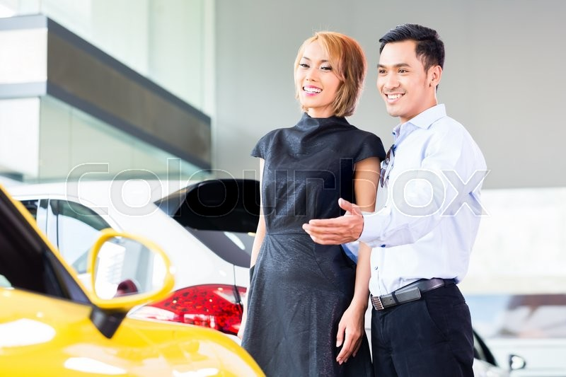Stock image of 'Asian couple choosing luxury sports car in auto dealership '