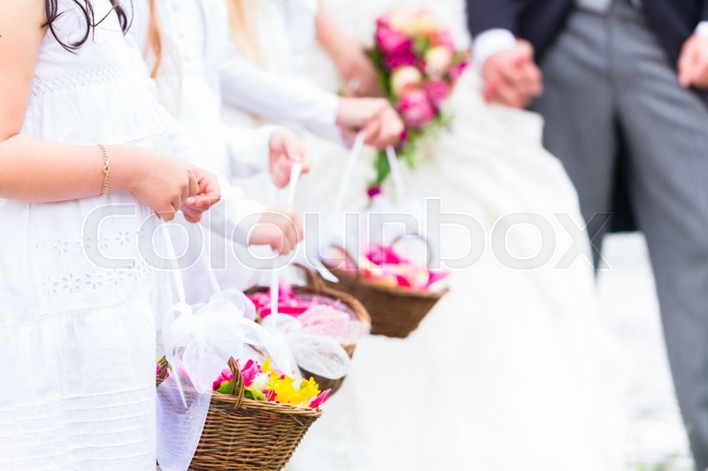Stock image of 'Wedding couple bride and groom with flower children or bridesmaid in white dress '
