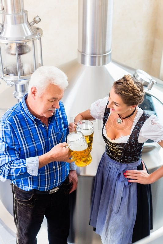 Stock image of 'Brewer and woman toasting in beer brewery'