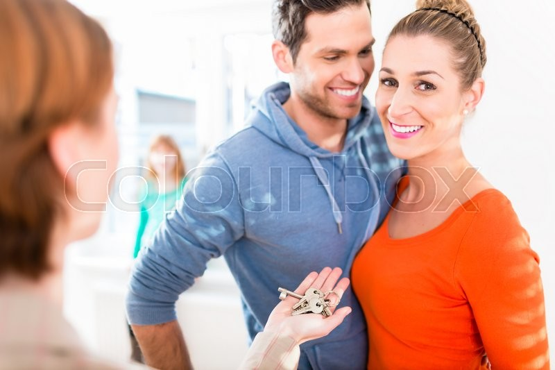 Stock image of 'Accommodation broker giving home key to family'
