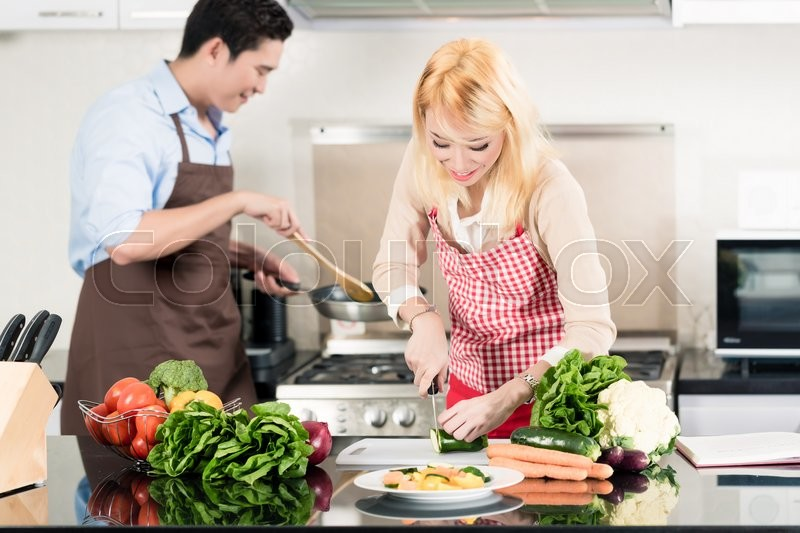 Stock image of 'Asian couple cooking in stylish and modern kitchen'