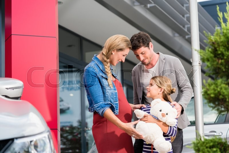 Stock image of 'Mother, father, and child buying car at dealership, a new family auto'