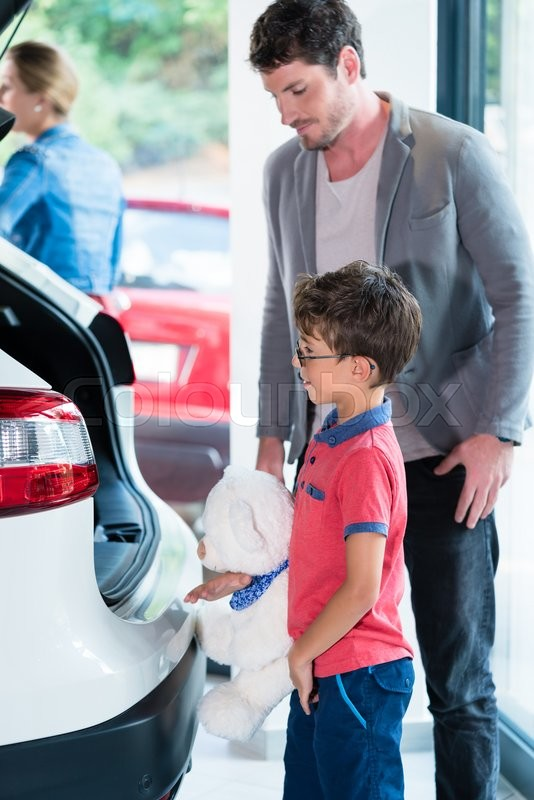 Stock image of 'Father and son checking trunk of new car in dealer showroom'