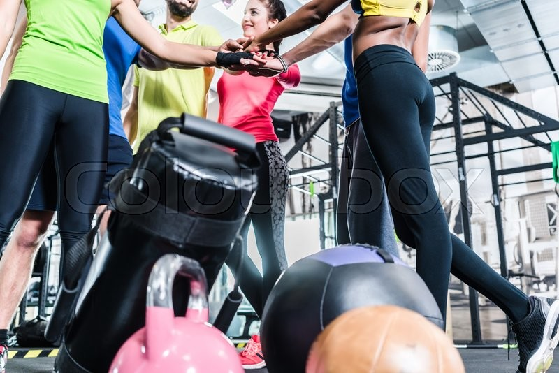 Stock image of 'Woman and men being motivated for fitness and sport stacking their hands'