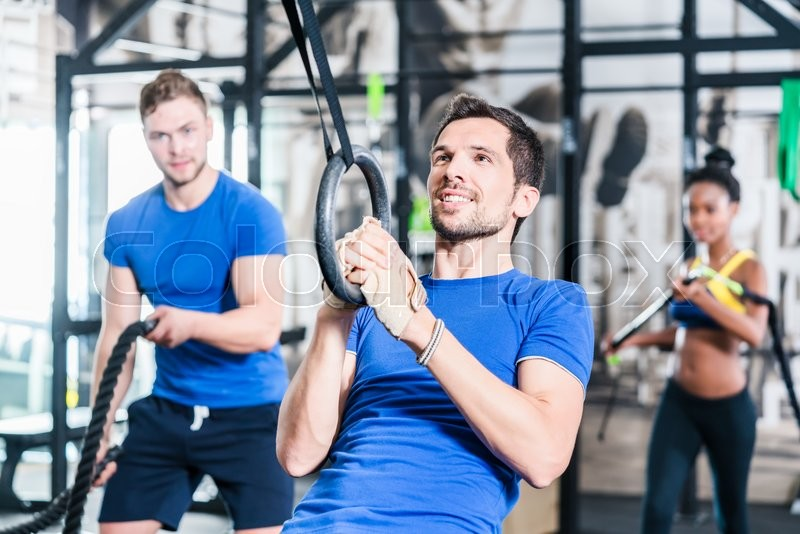 Stock image of 'Man at rings doing fitness exercise in gym'