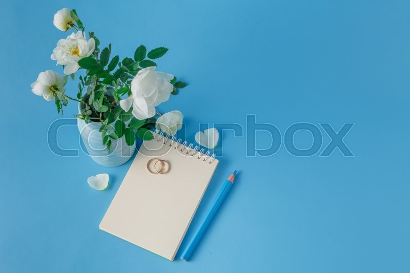 Stock image of 'Wedding rings and wild roses bouquet'
