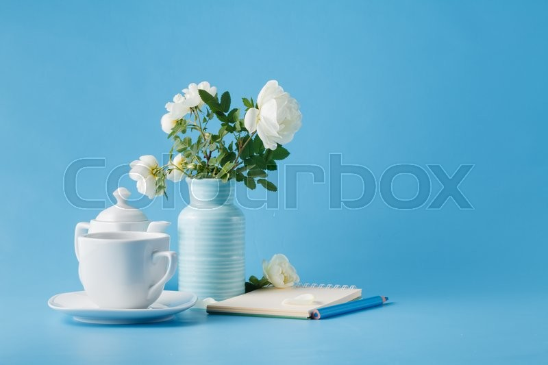 Stock image of 'Delicate bouquet of wild rose and cup of tea'